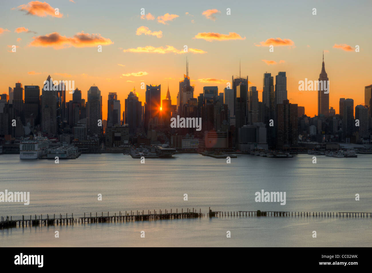 The rising sun shines through the buildings of the mid-town Manhattan skyline at sunrise as viewed New Jersey. - Stock Image