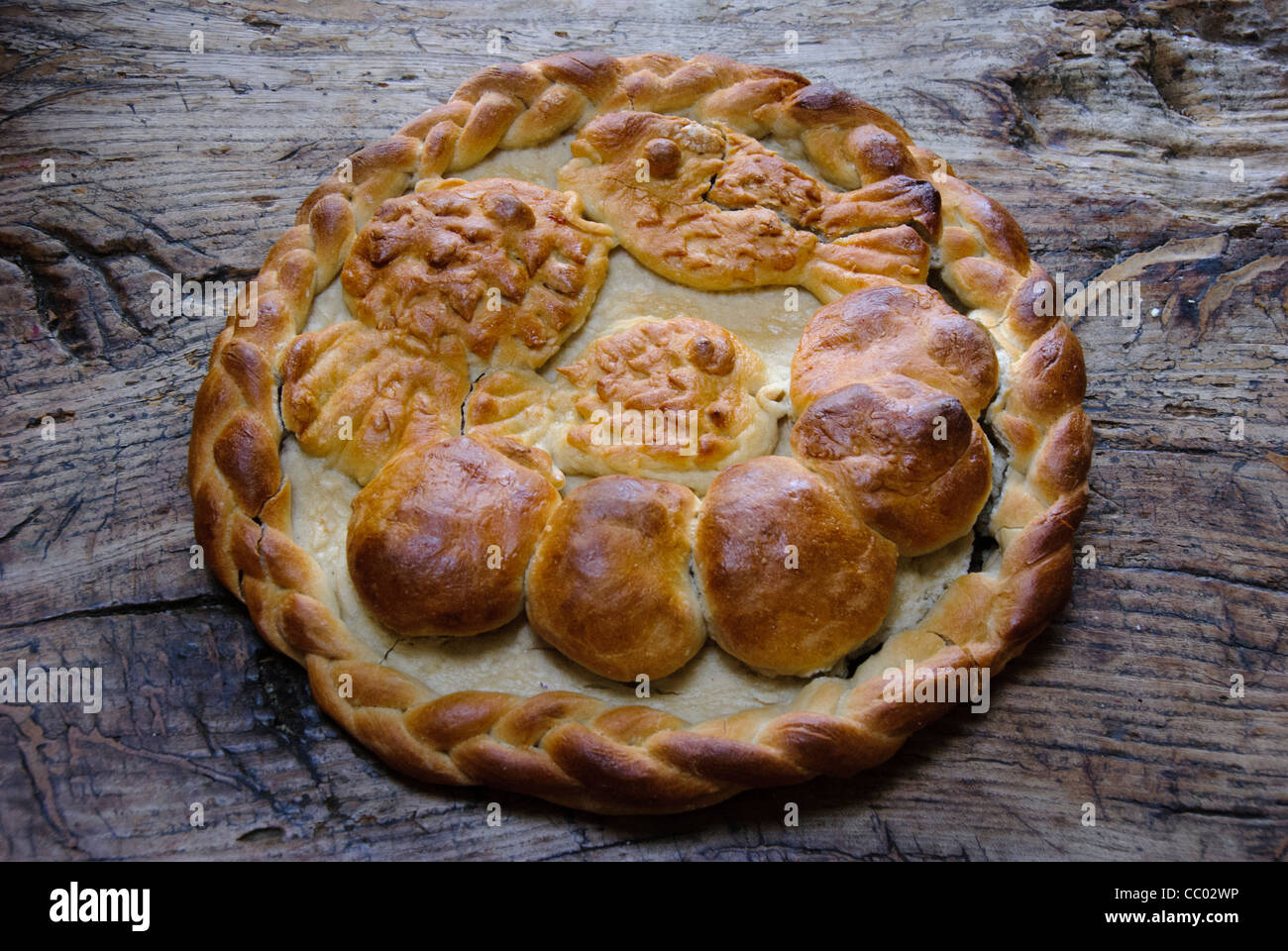 Home made ornamental harvest loaf with motif of five loaves and two fishes and plaited edge - Stock Image