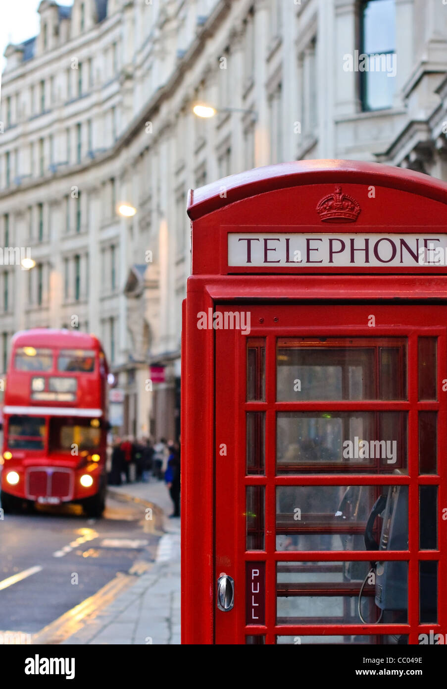 Traditional London old red telephone box and old double decker in background. - Stock Image