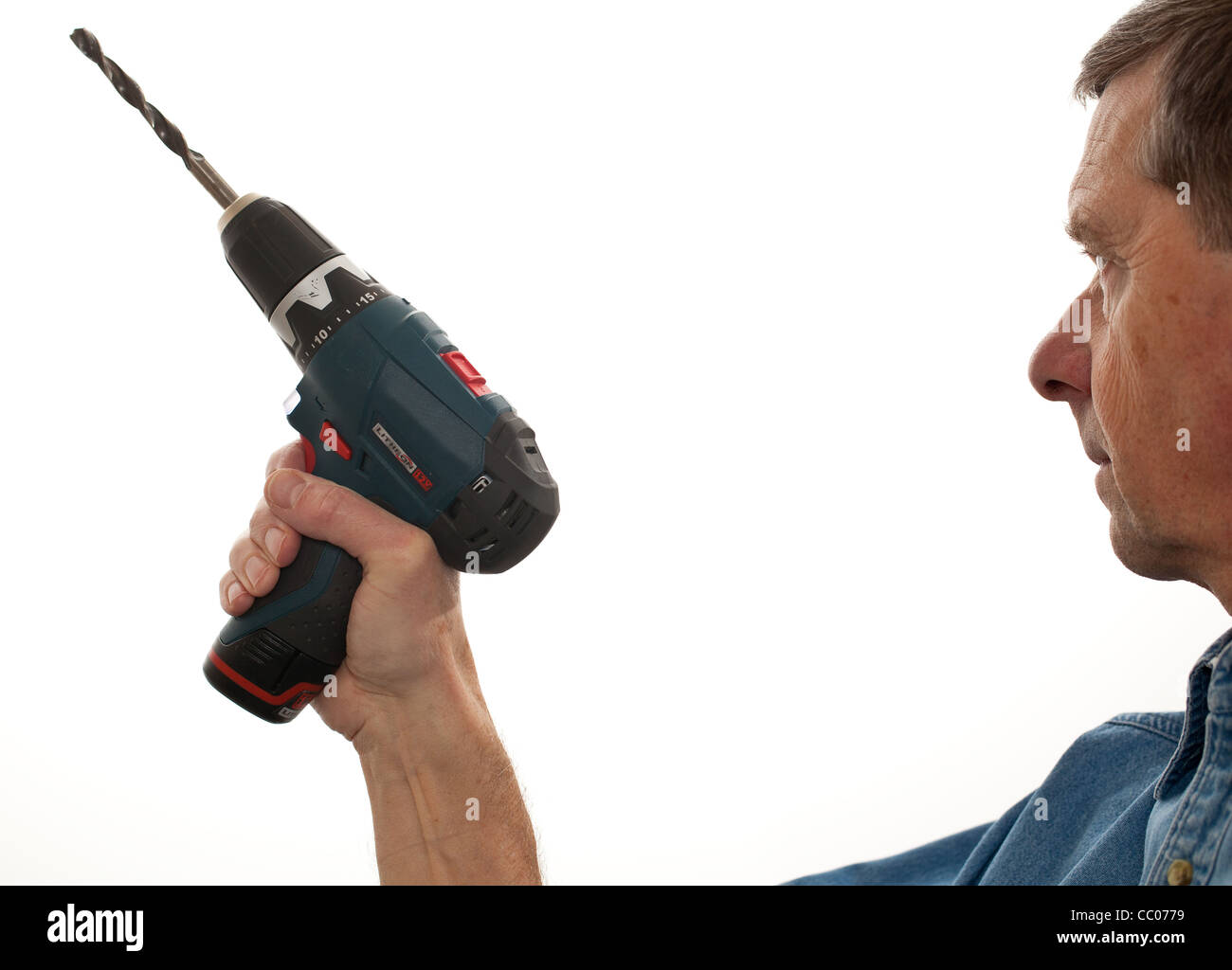 Man holding a power drill isolated against white - Stock Image