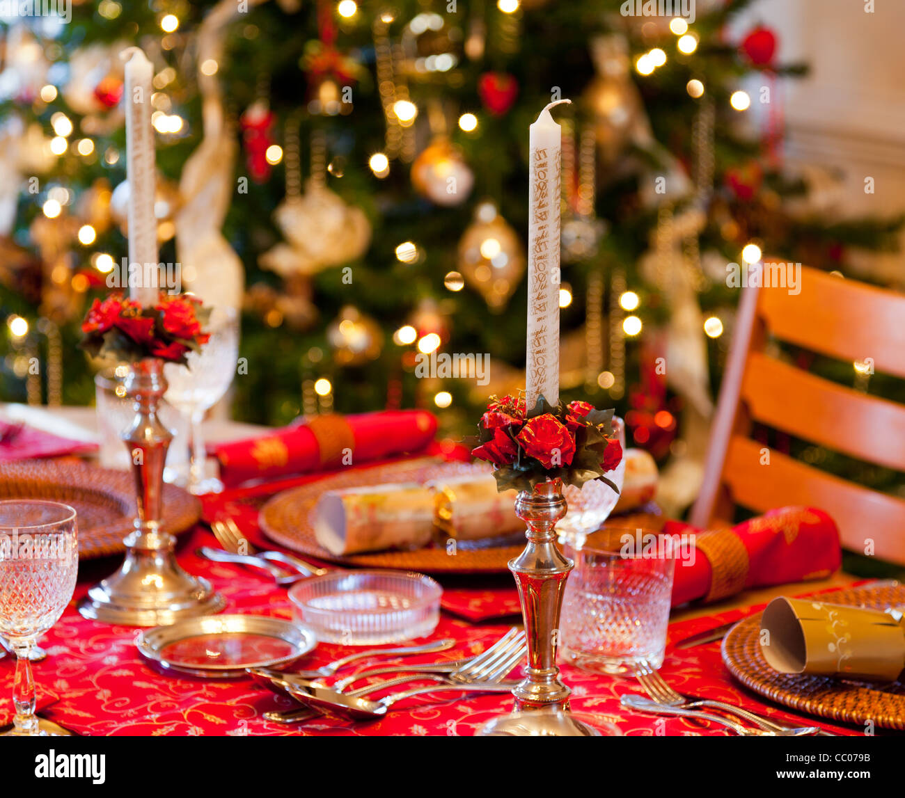 Christmas table setting for Christmas dinner with candles, crackers ...