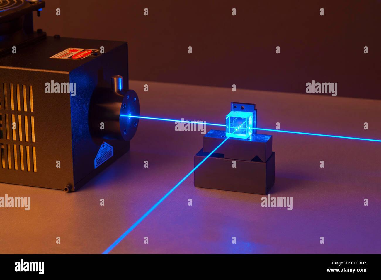 argon ion laser beam passing through a beam splitter - Stock Image