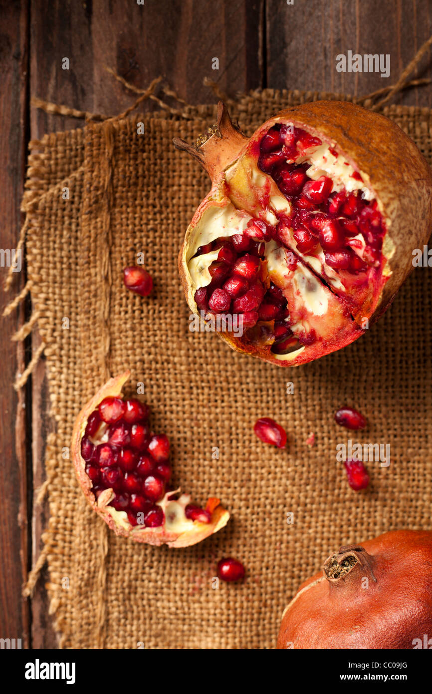 Pomegranate with Seeds on Jute and Wood - Stock Image