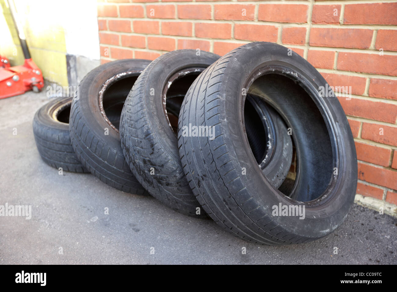 four part worn old used tires lying outside a garage in London England UK United kingdom - Stock Image