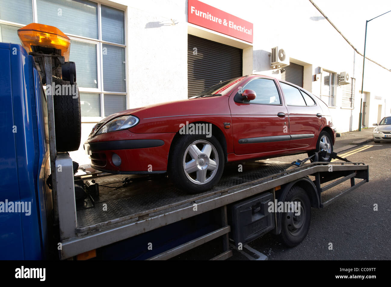 renault megane car attached to the back of a car transport recovery vehicle on street London England UK United kingdom - Stock Image