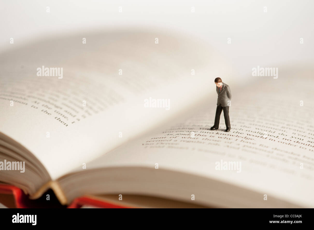 a small figure of a man walking on an open book - conceptual image for literacy and reading - Stock Image