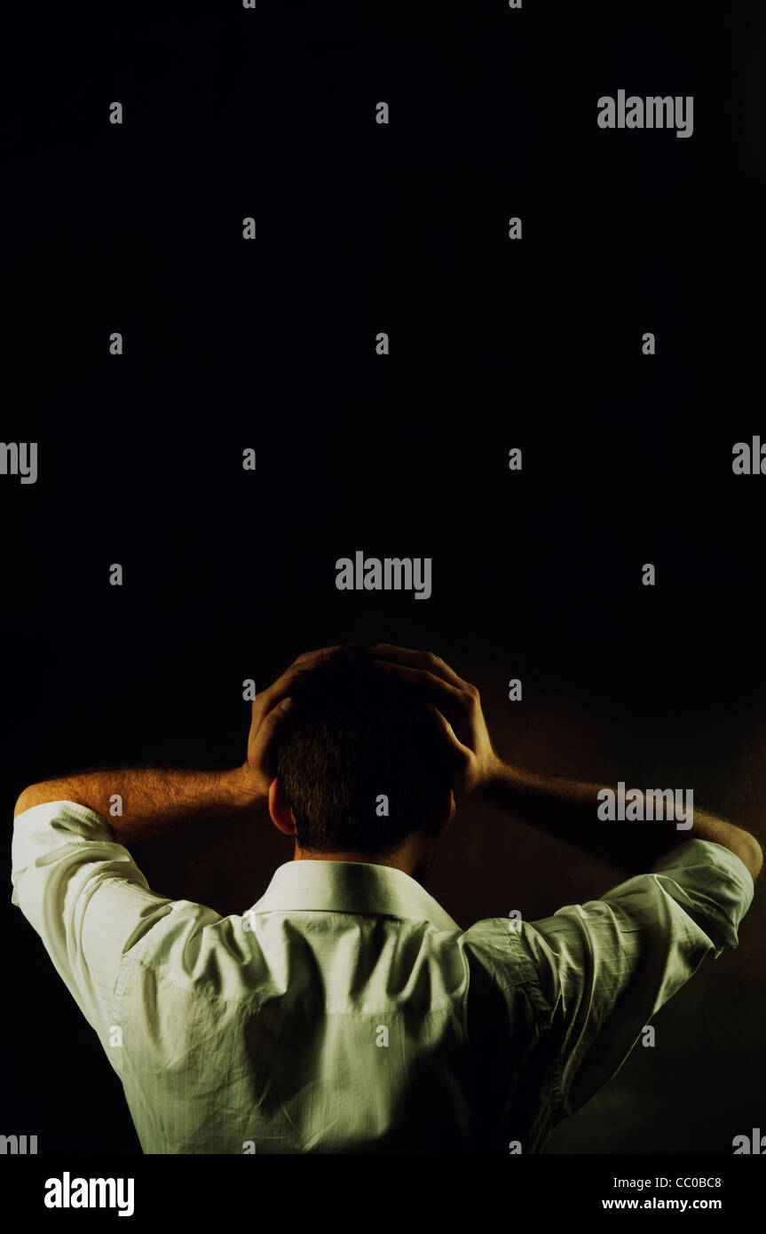 Rear view of a man head in hands - Stock Image