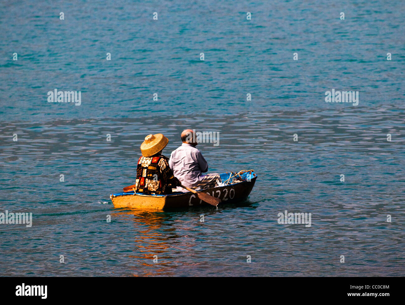 An old Chinese couple in their small boat. - Stock Image