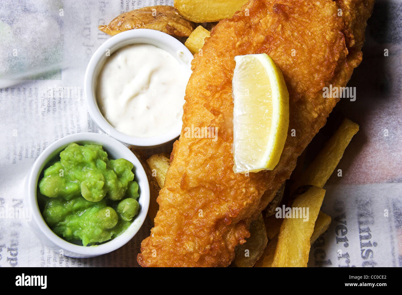 Fish chips and peas with a slice of lemon and tartar sauce dip - Stock Image