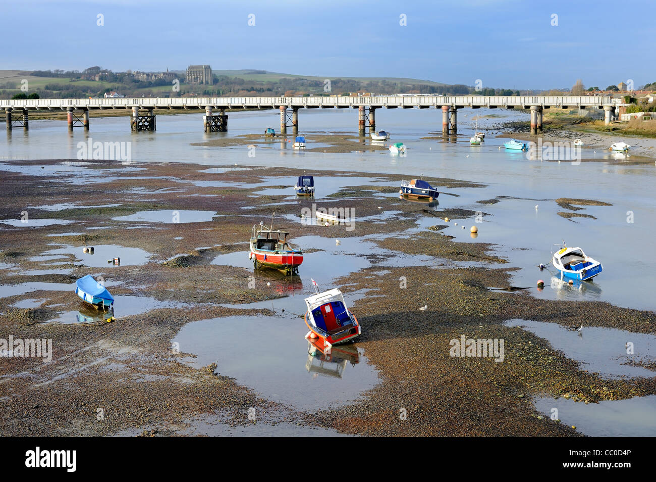 Boats stranded at low tide on river Adur with railway bridge and Lancing college in Background Stock Photo
