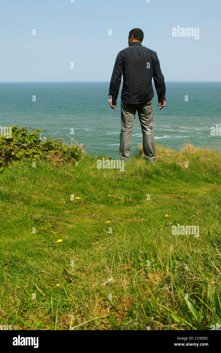 Man standing on a cliff by the sea - Stock Image