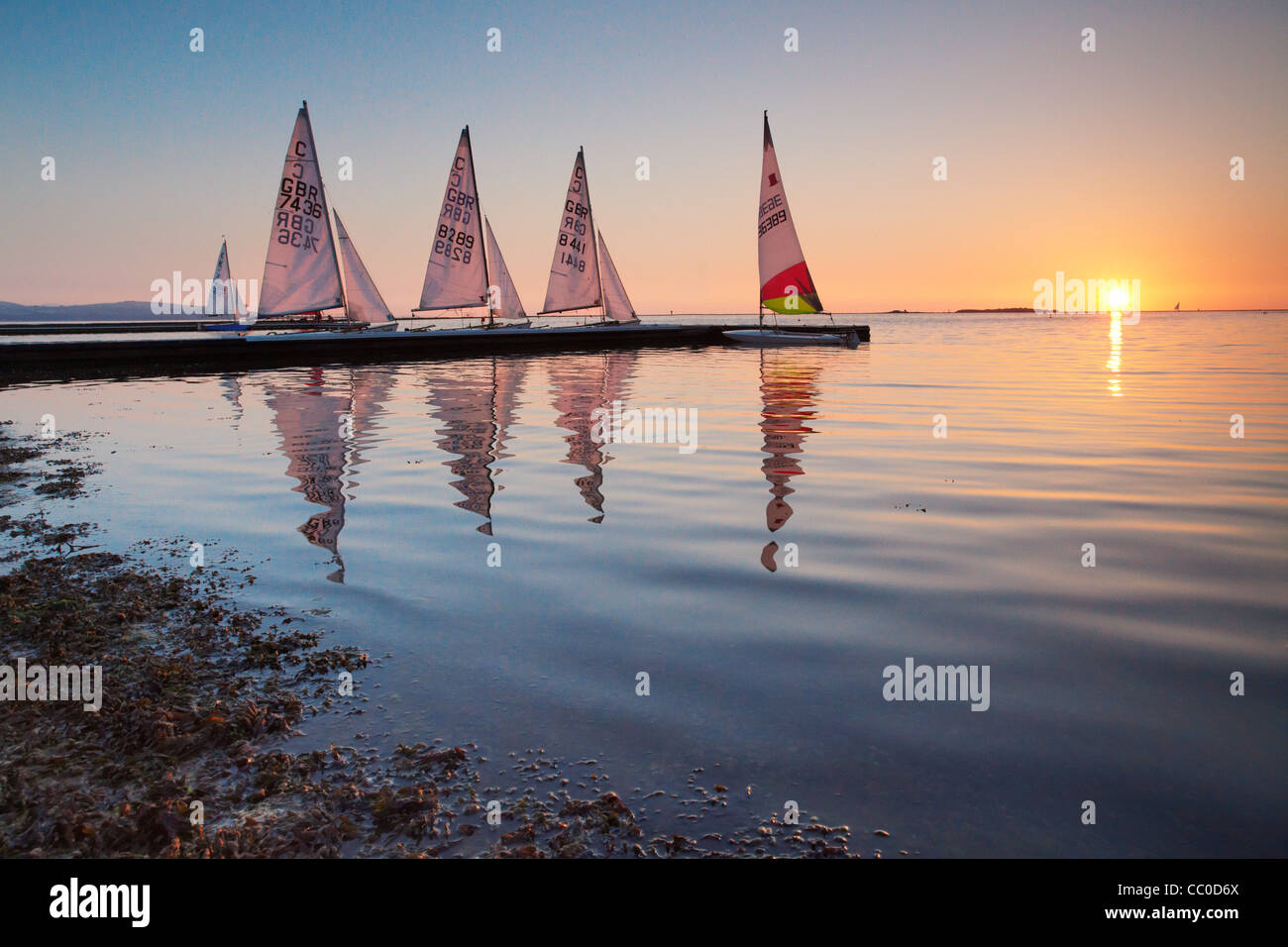 Sailing boats moored at sunset on the marine lake at West Kirby, Wirral, UK - Stock Image