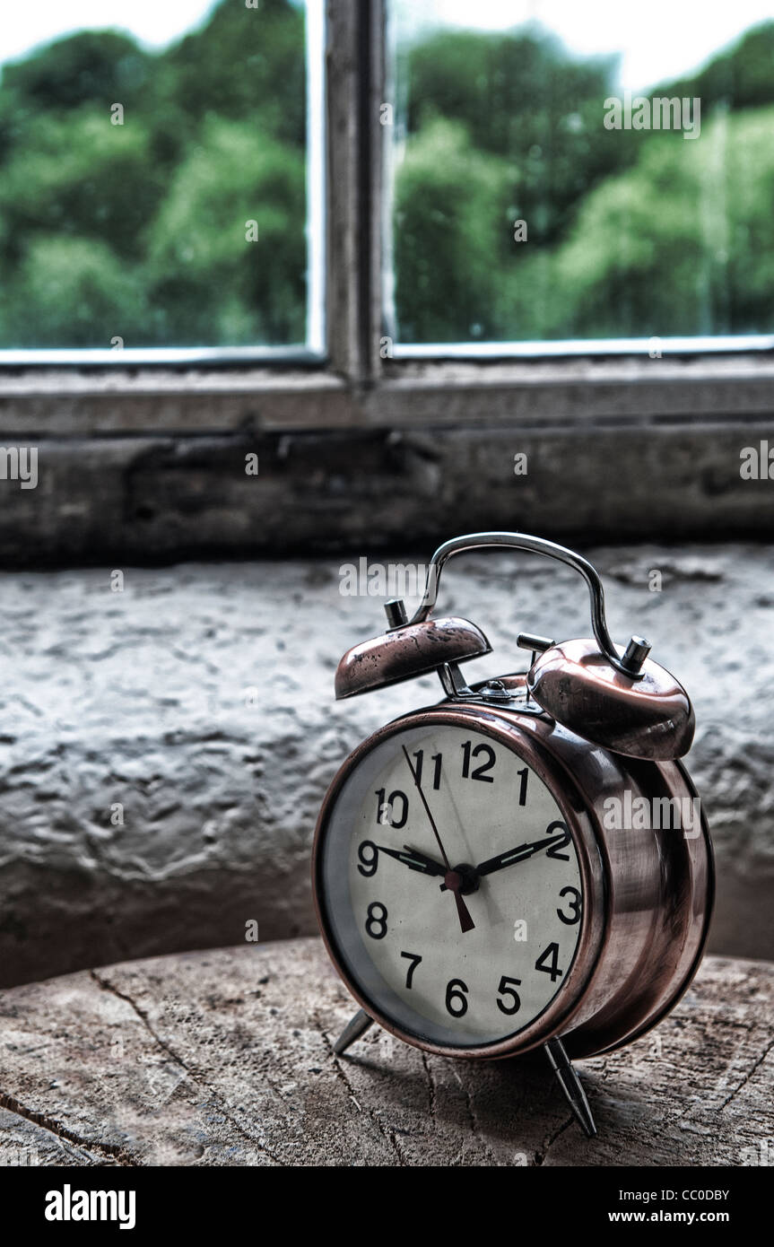 Vintage metal alarm clock by the window - Stock Image