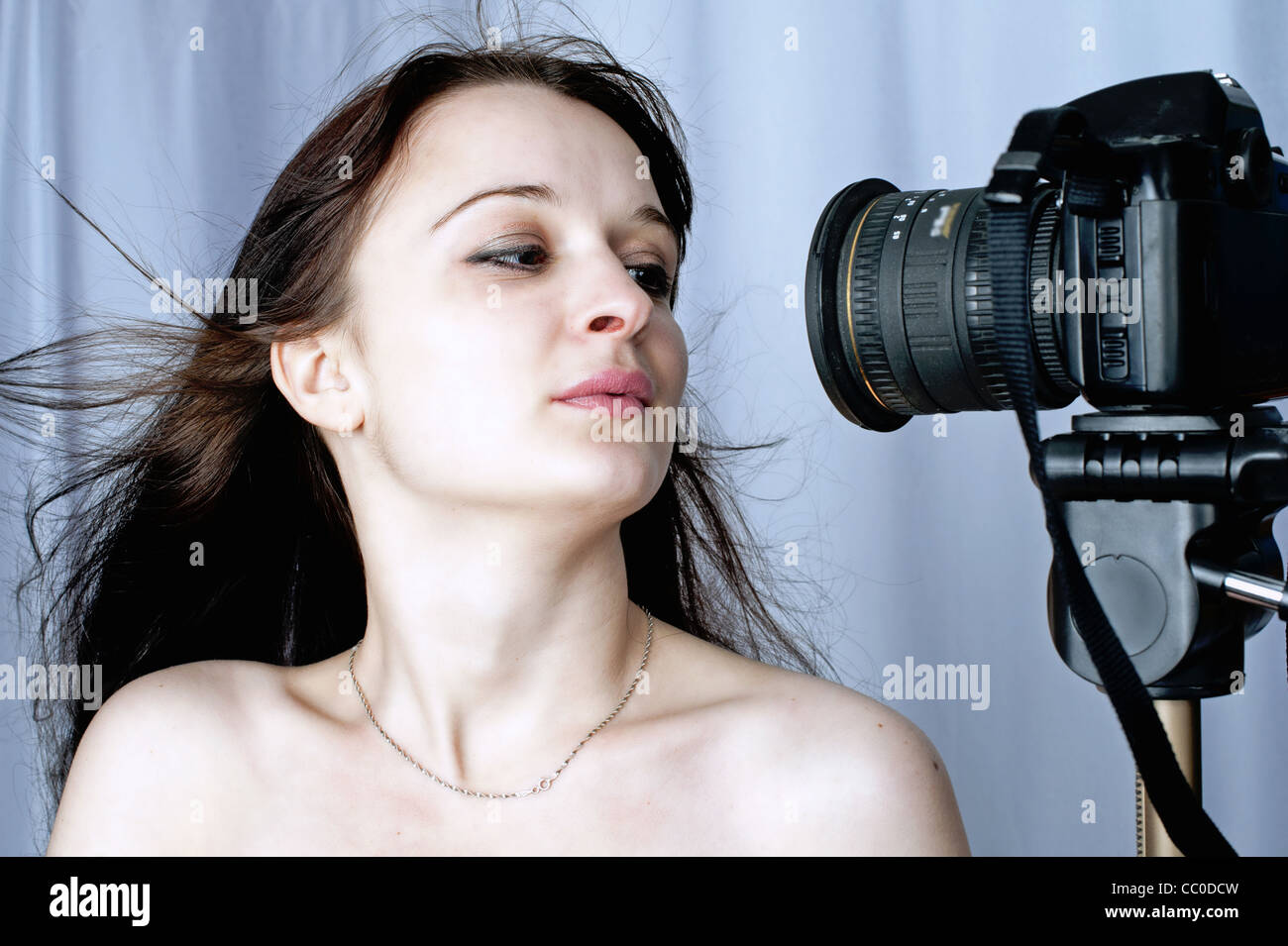 a photo-model sits before a photo-camera Stock Photo