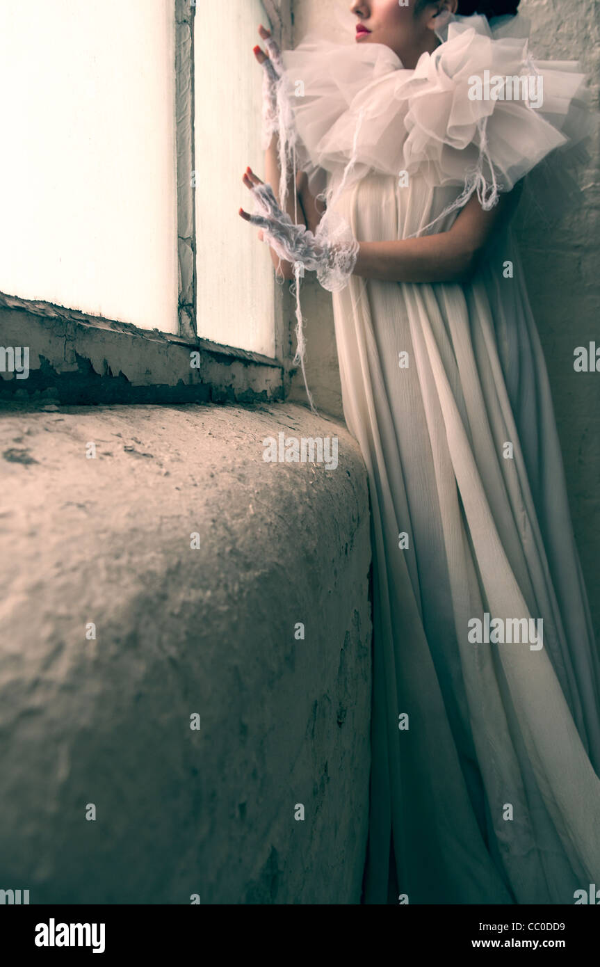 Sad young woman wearing vintage dress waiting by the window - Stock Image