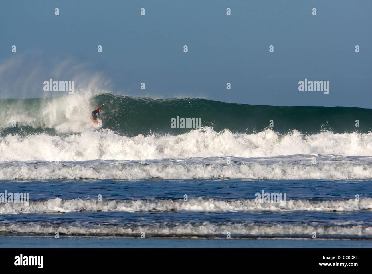 A surfer on a big wave at Porthtowan beach, Cornwall. - Stock Image
