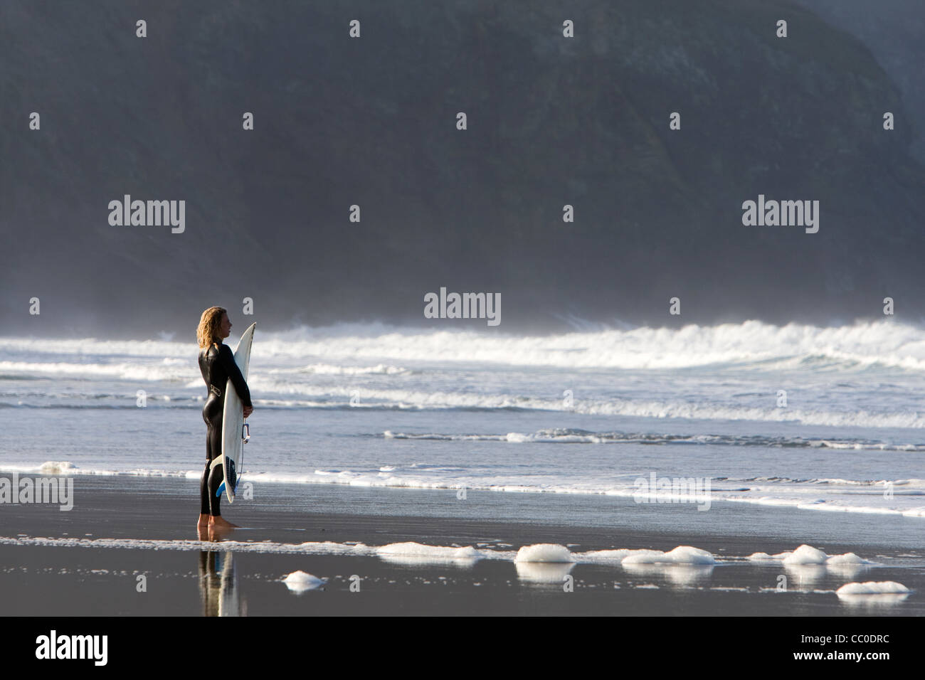 A surfer looks at the surf conditions at Porthtowan beach, Cornwall. - Stock Image