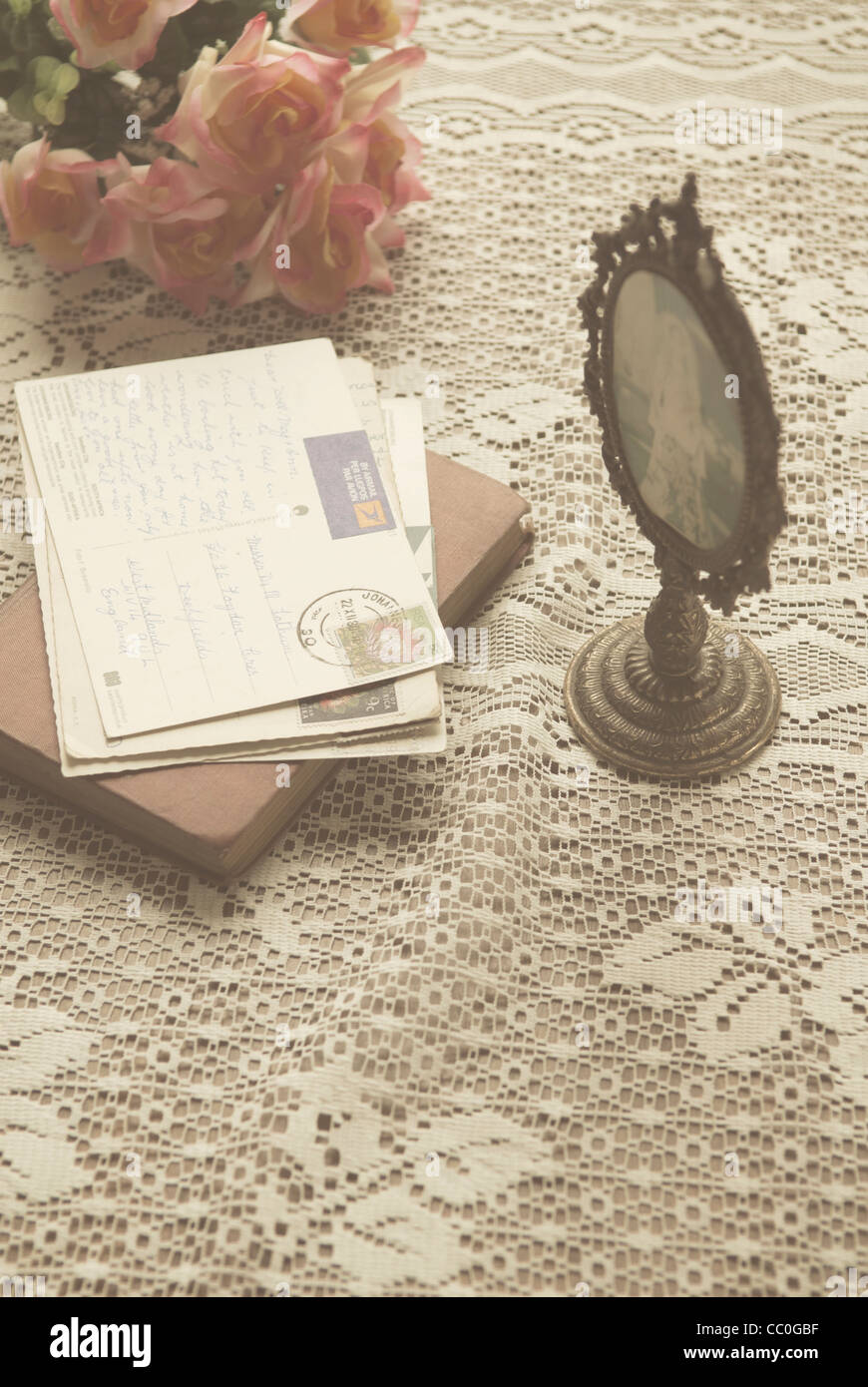 Old postcards over a book next to oval shaped picture frame and roses - Stock Image
