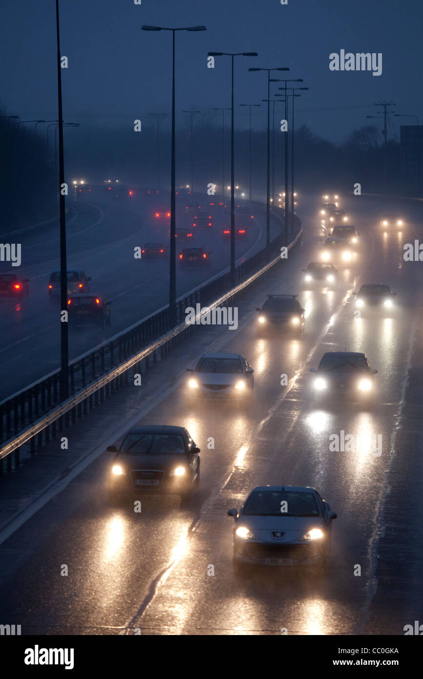 Cars and traffic on a wet raining evening on uk motorway.Driving in dangerous winter conditions. - Stock Image
