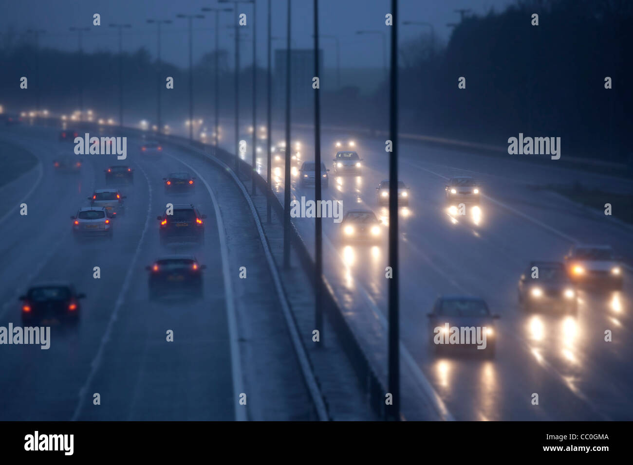 Cars and traffic on a wet raining evening on uk motorway, Driving in dangerous winter conditions. - Stock Image