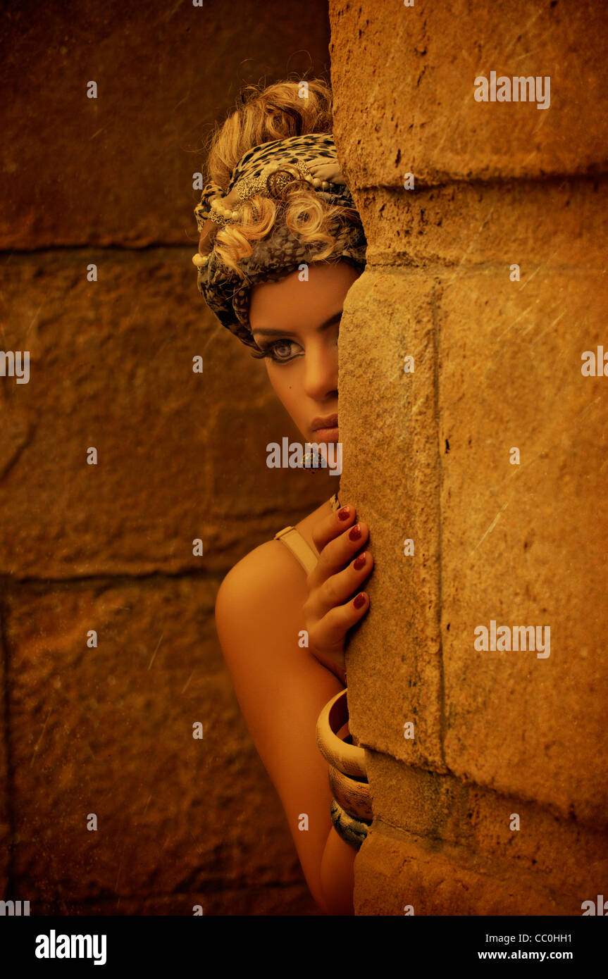 Young girl hiding behind wall Stock Photo