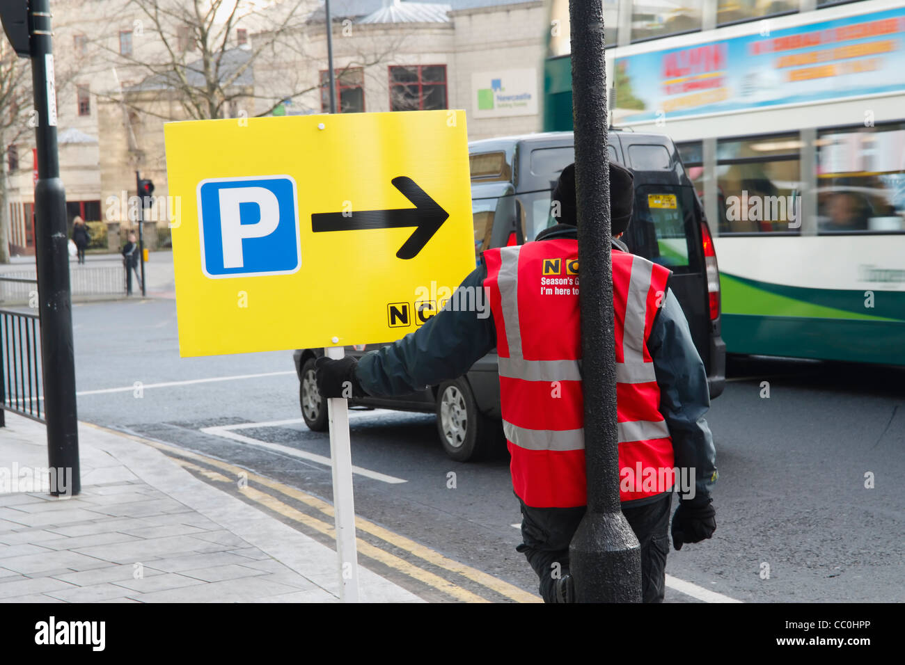Man with placard showing directions to NCP parking in Newcastle Upon Tyne at christmas - Stock Image