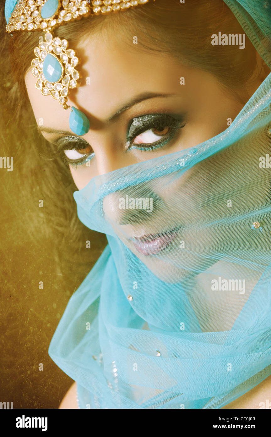 Serious Indian woman covering her face with blue veil looking away Stock Photo