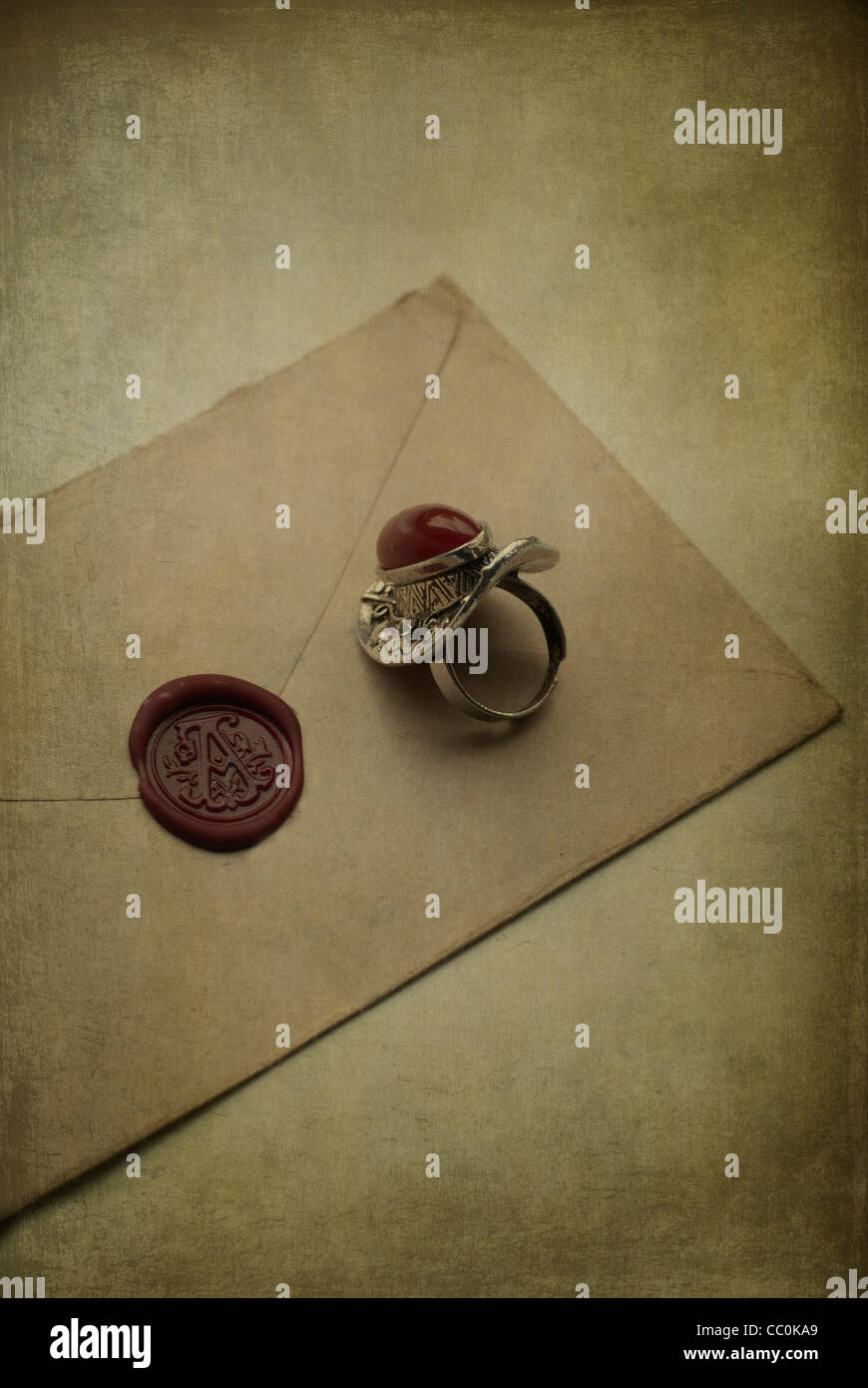 Old ring over a brown envelope sealed with red wax - Stock Image