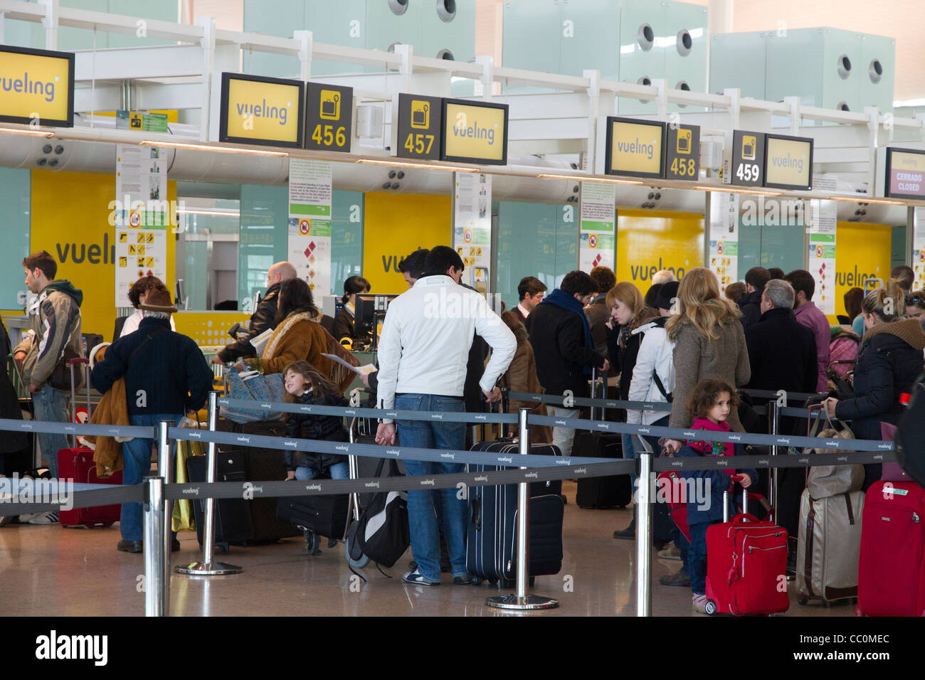 People at Vueling check in desks in Barcelona airport Spain - Stock Image