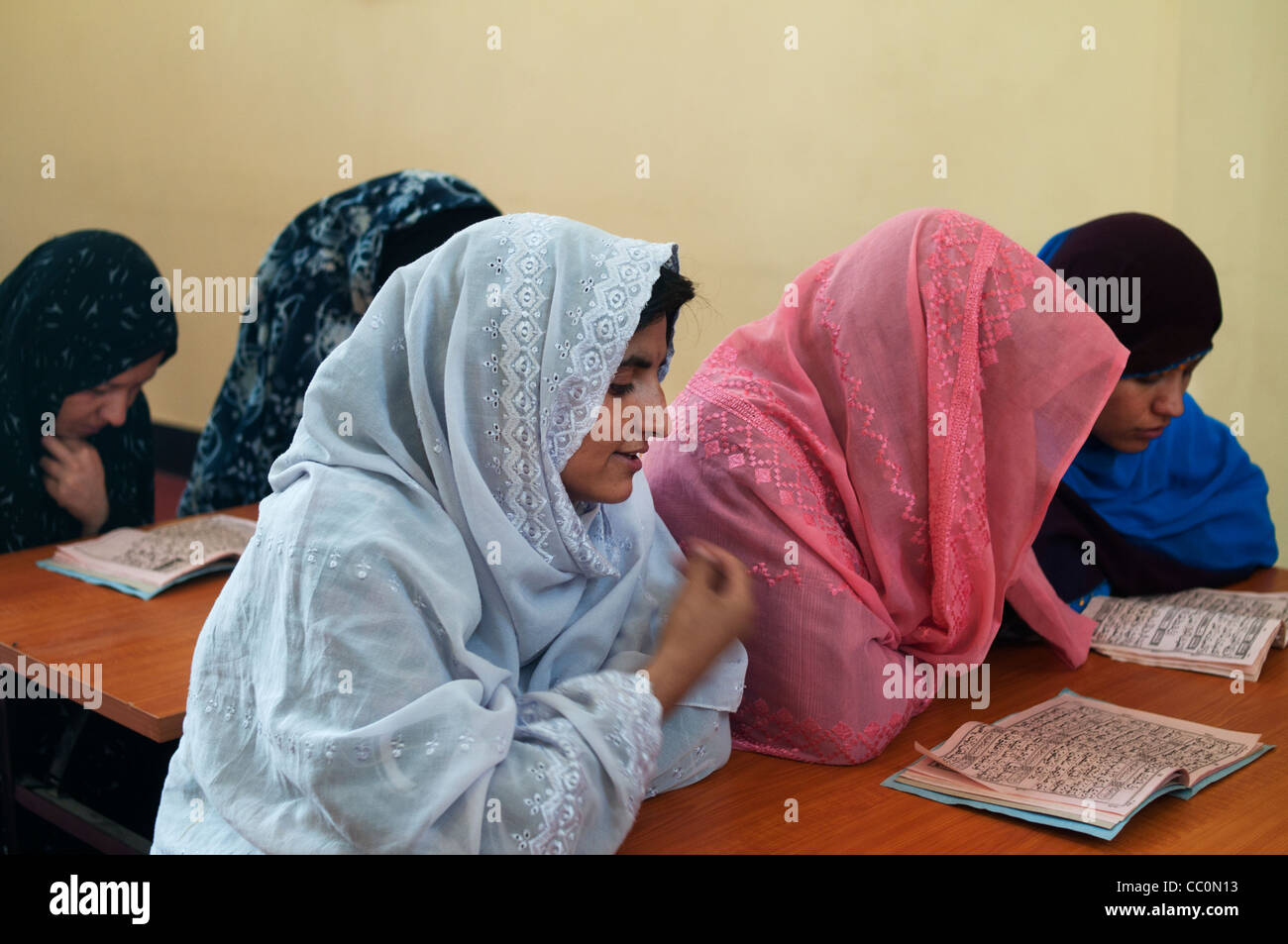 Herat Women's prison. Women prisoners reading the Holy Koran. - Stock Image