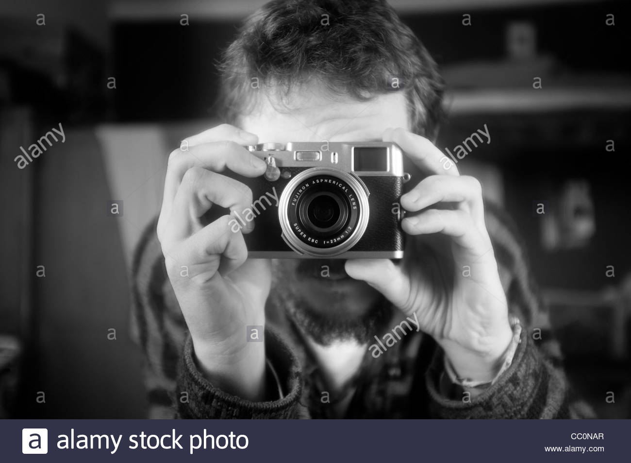Man taking a photos with a Fuji x100 digital camera - Stock Image