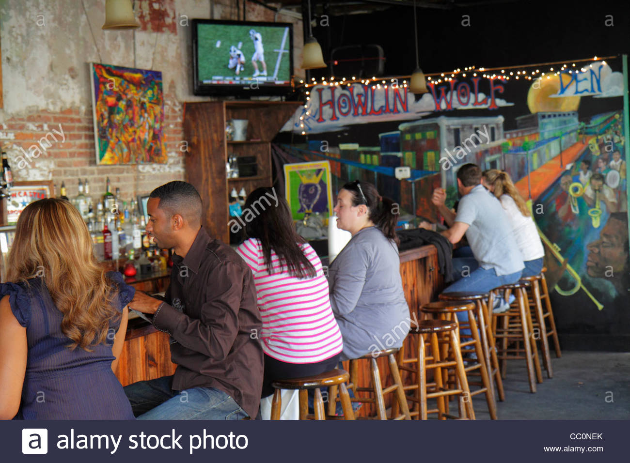 New Orleans Louisiana Warehouse District Howlin Wolf Den bar lounge live music venue business barstool Black man - Stock Image