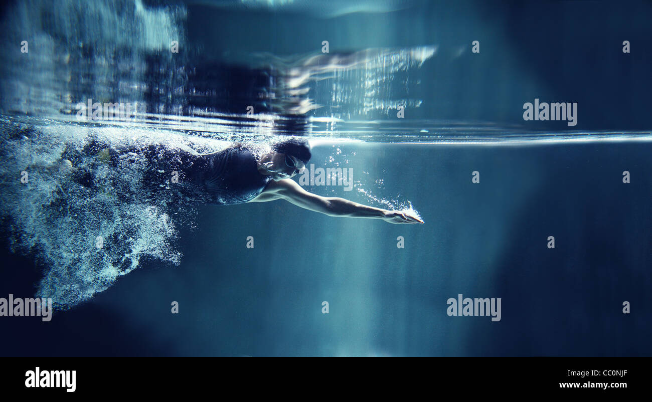 professional swimmer crawl underwater isolated blue background - Stock Image