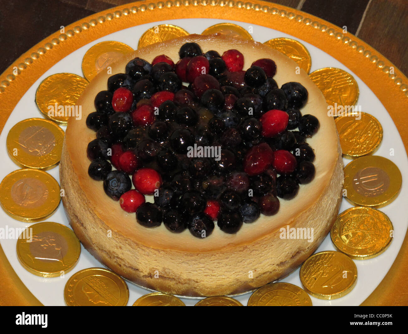 Cheesecake with cranberries and blueberries on top, circled with chocolate gold coins of Euros. - Stock Image