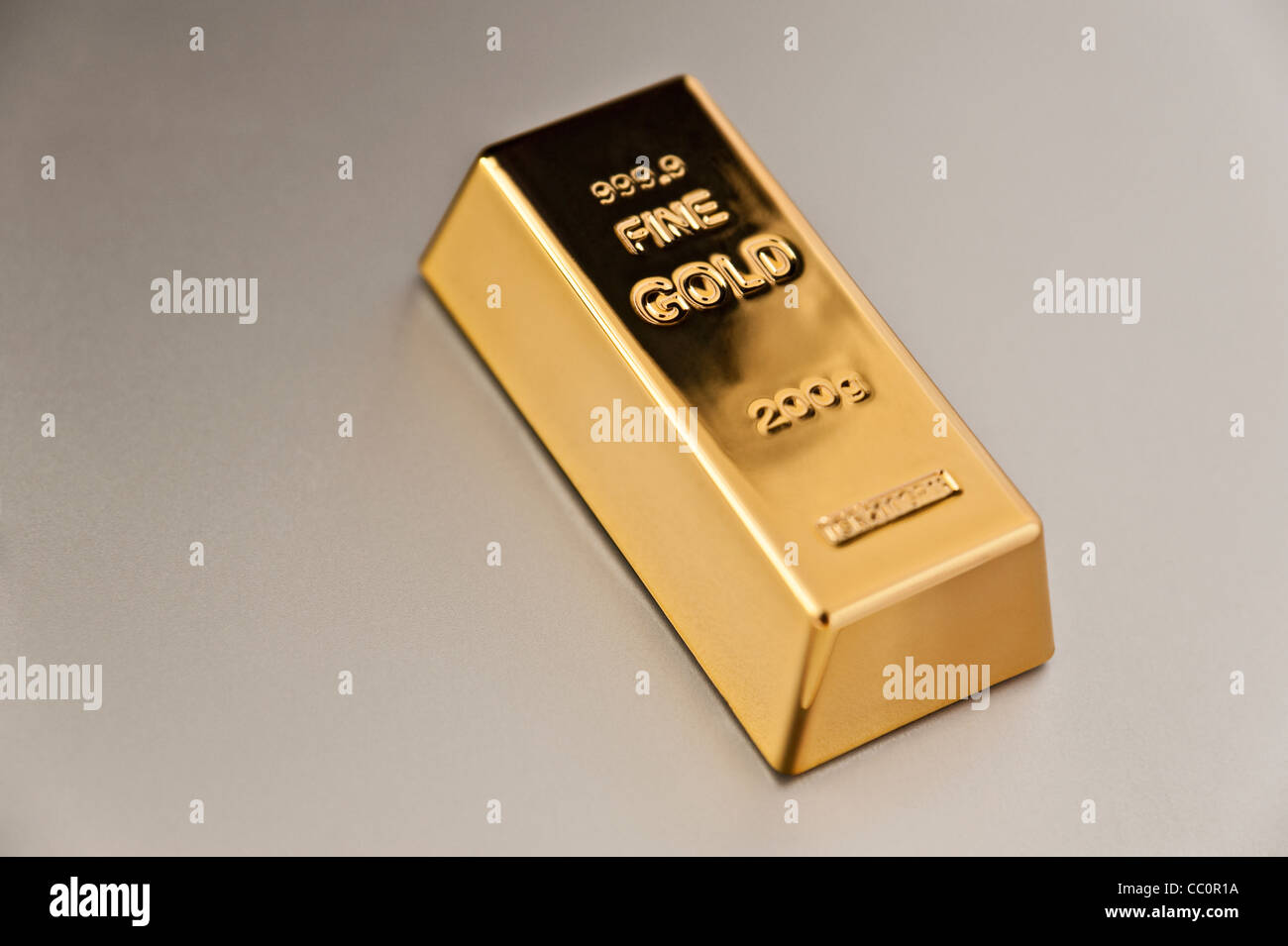 Fine Gold Bar on a silver background - Stock Image