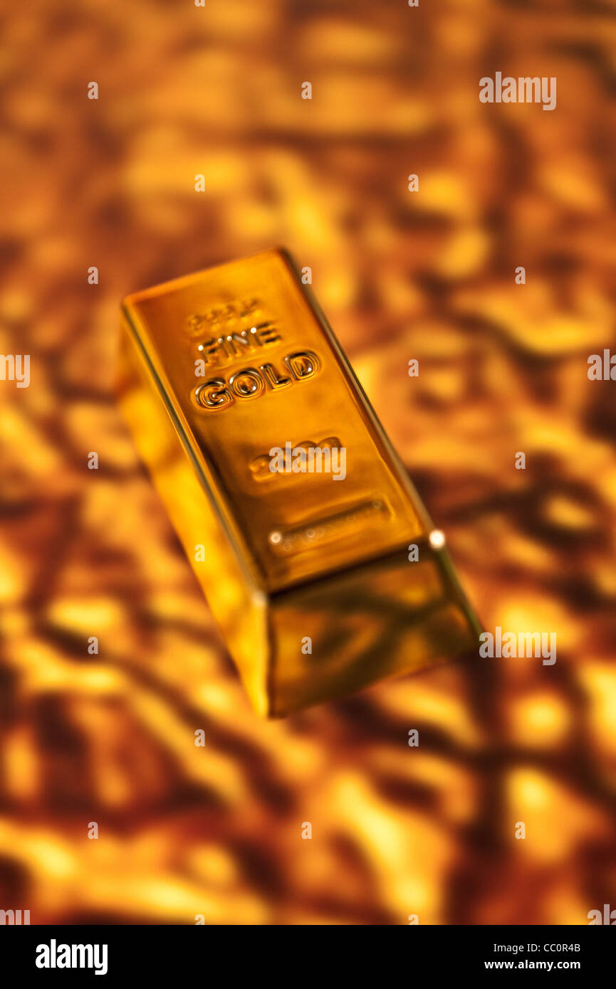 Fine Gold Bar on a molten gold background - Stock Image