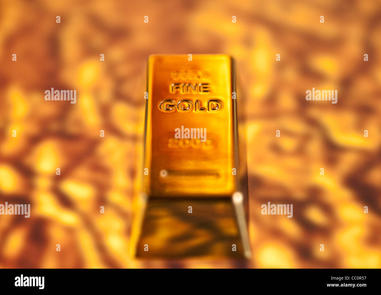 Fine Gold Bar rising out of a molten gold background - Stock Image