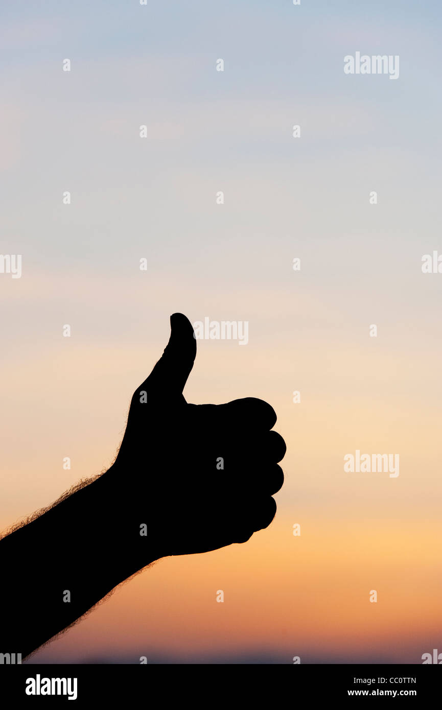 Thumbs up hand silhouette against sunrise sky - Stock Image