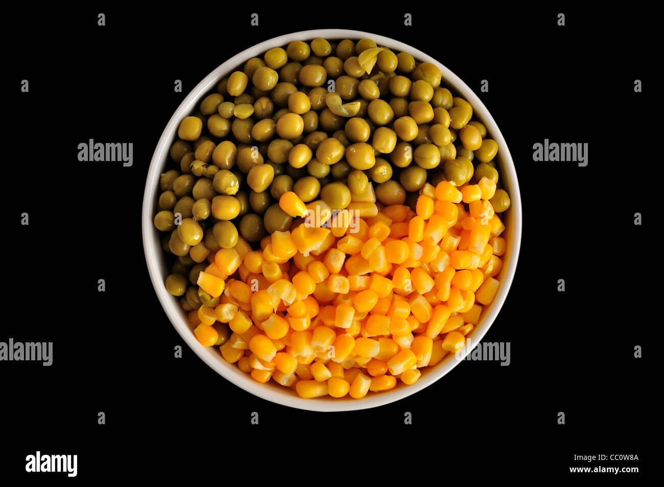 a plate with corn and peas, isolated, on a black background Stock Photo