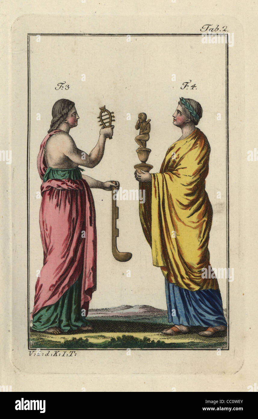 Egyptian woman with sacred sistrum rattle and simpulum ladle, and priestess with statue of Harpocrates, the god - Stock Image