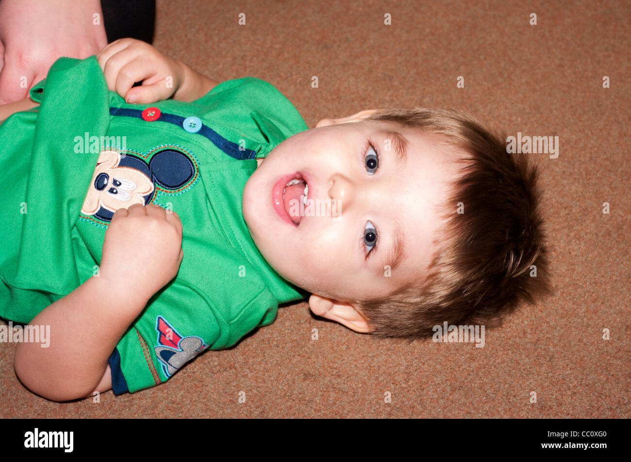 2 Year Old Young Child Boy Infant Toddler Laying On The Floor Looking At THe Camera With His Mouth Open - Stock Image