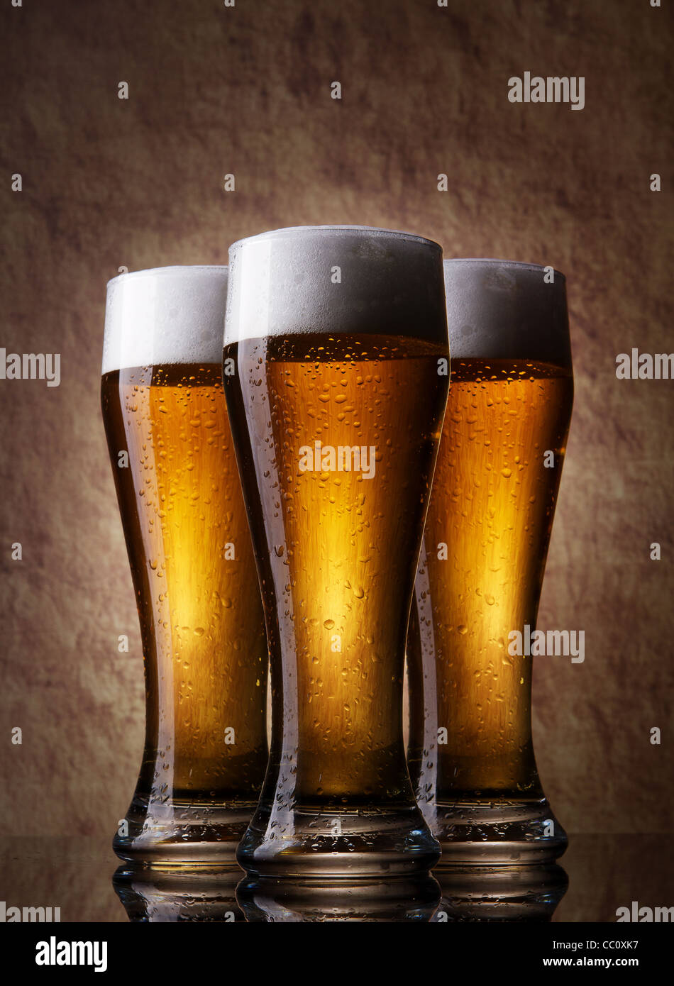 Three cold Beer into glass on a old stone - Stock Image