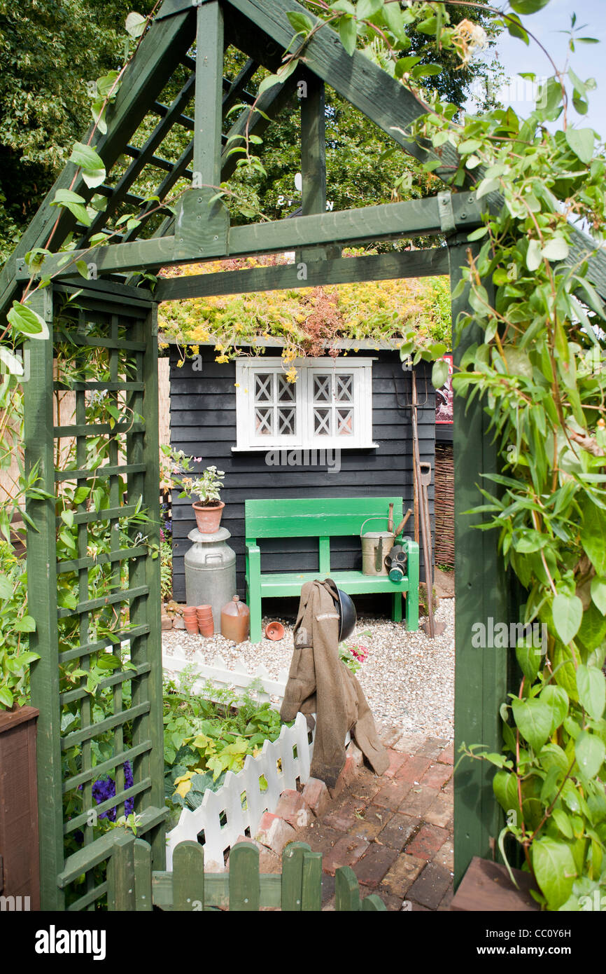 Wooden arch entrance to the small kitchen garden. - Stock Image