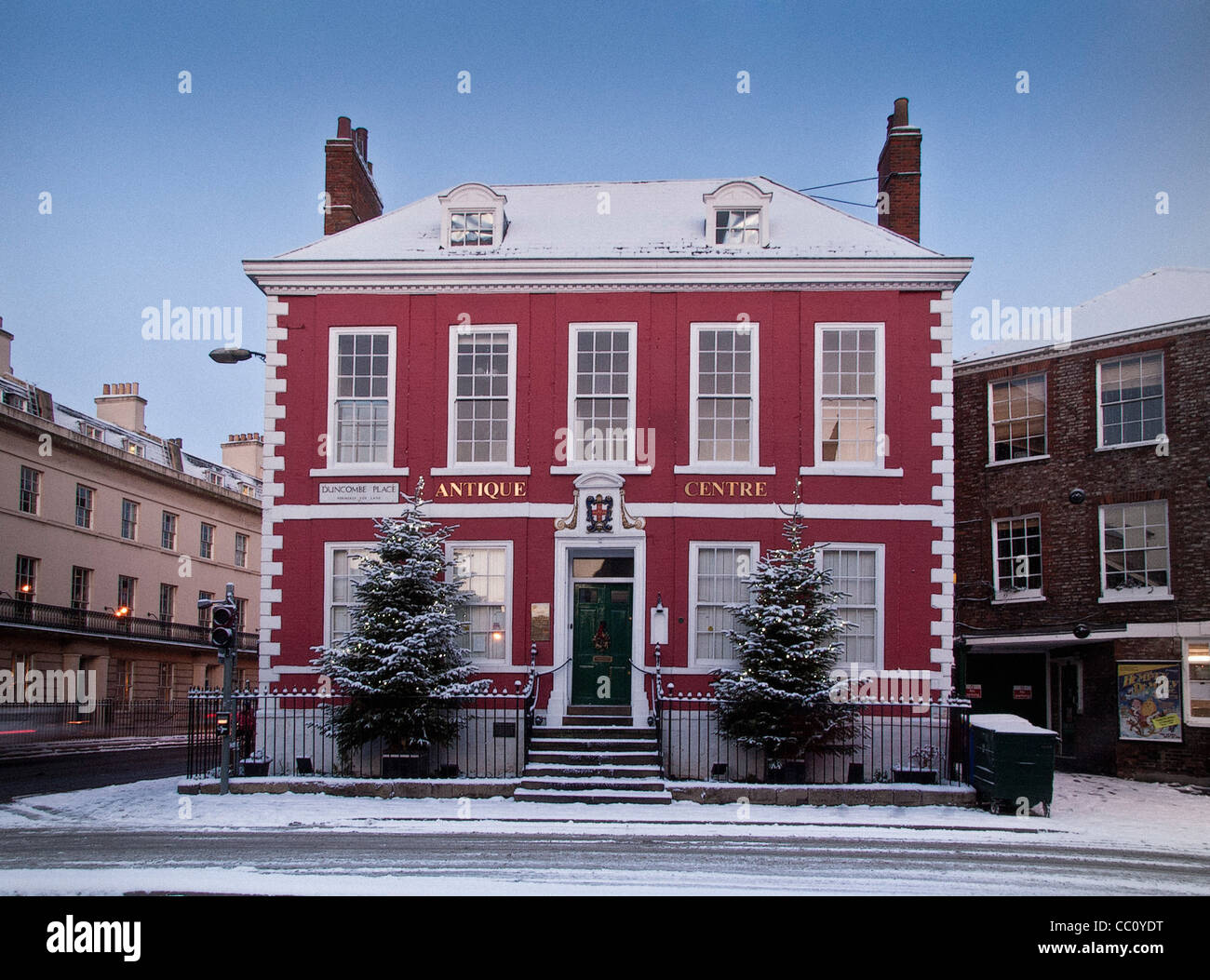Red House Antiques centre in snow with Christmas trees - Stock Image