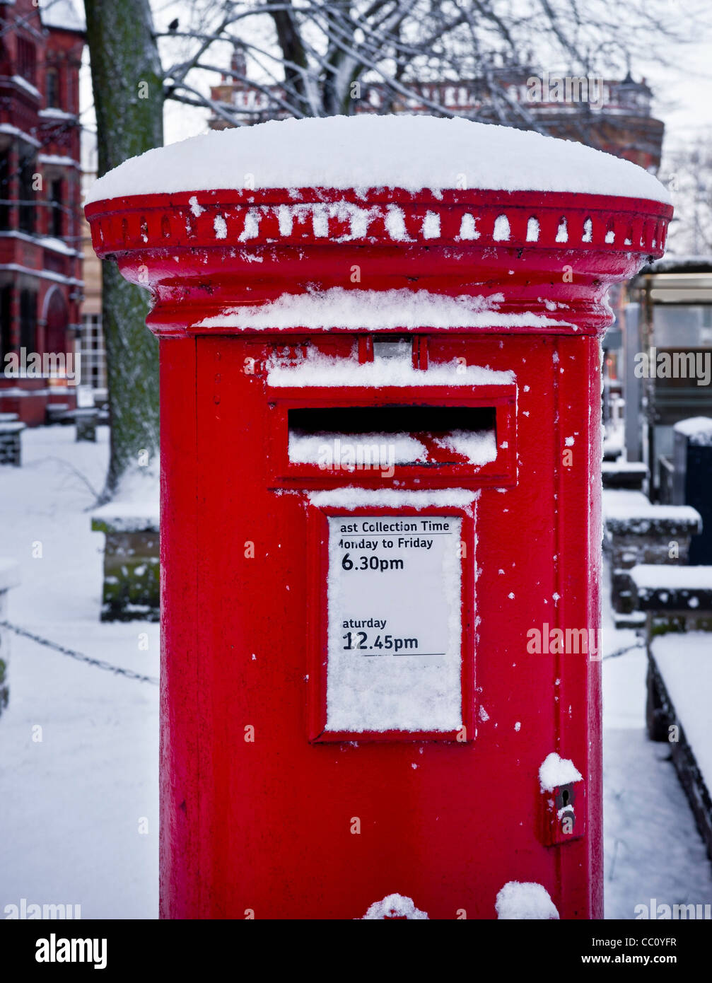 Red postbox in snow, York - Stock Image