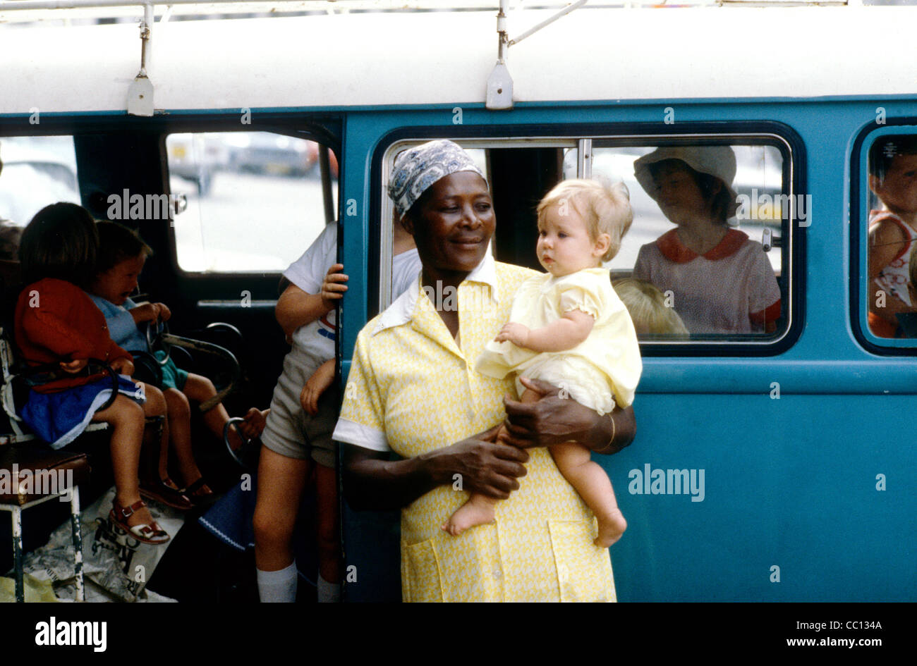 A black nanny looking after white children at a Zimbabwe sporting event - Stock Image