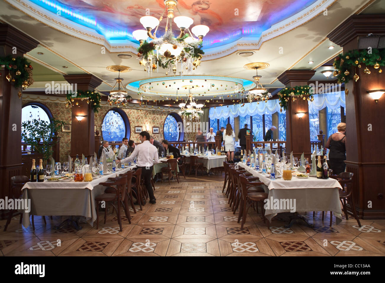 Russian Restaurant. Detail Of A Fancy Table Set For Christmas Dinner Party  For Lot Of Persons. Waiters Serving Tables