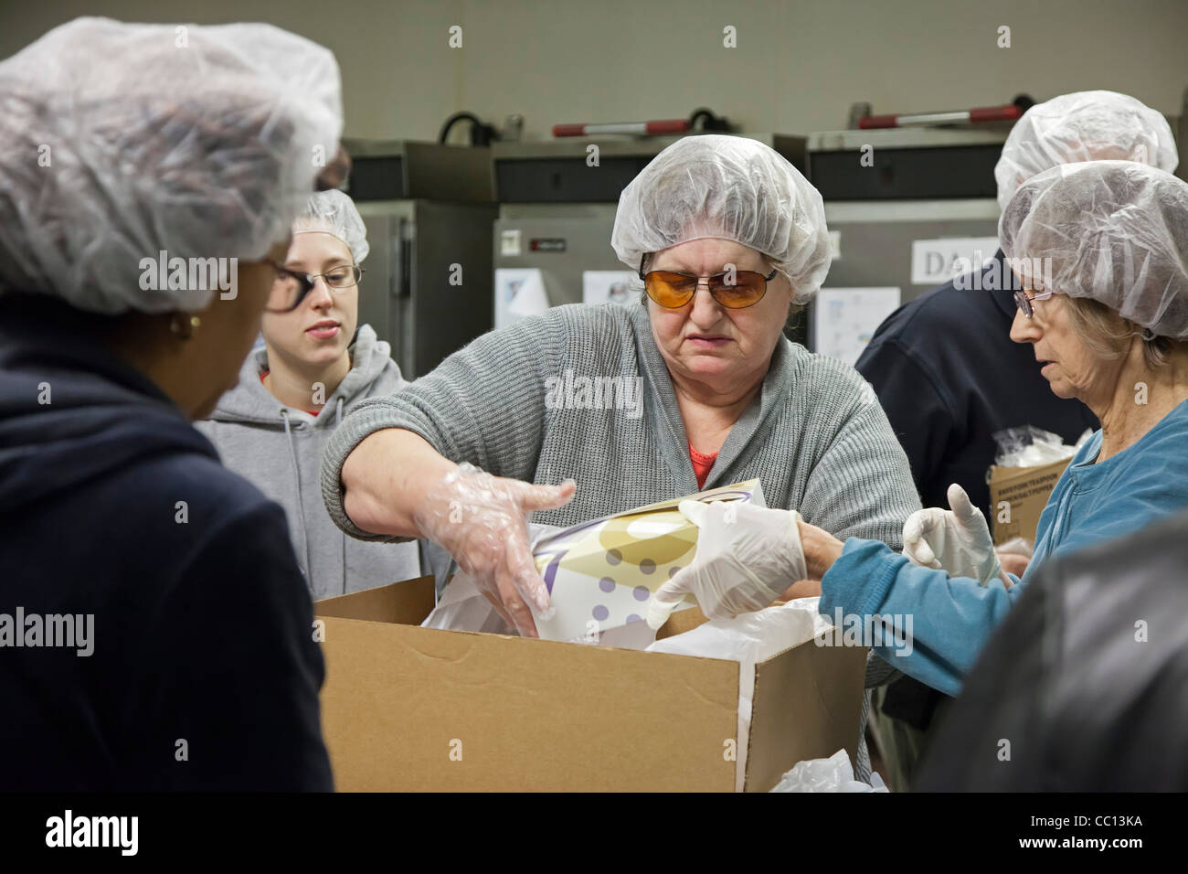 Volunteers pack Christmas meals for homebound senior citizens - Stock Image
