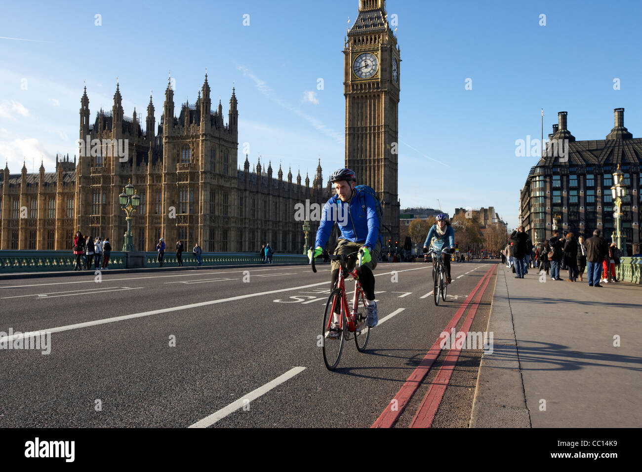 cyclists crossing westminster bridge cycle lane outside the palace of westminster houses of parliament buildings - Stock Image