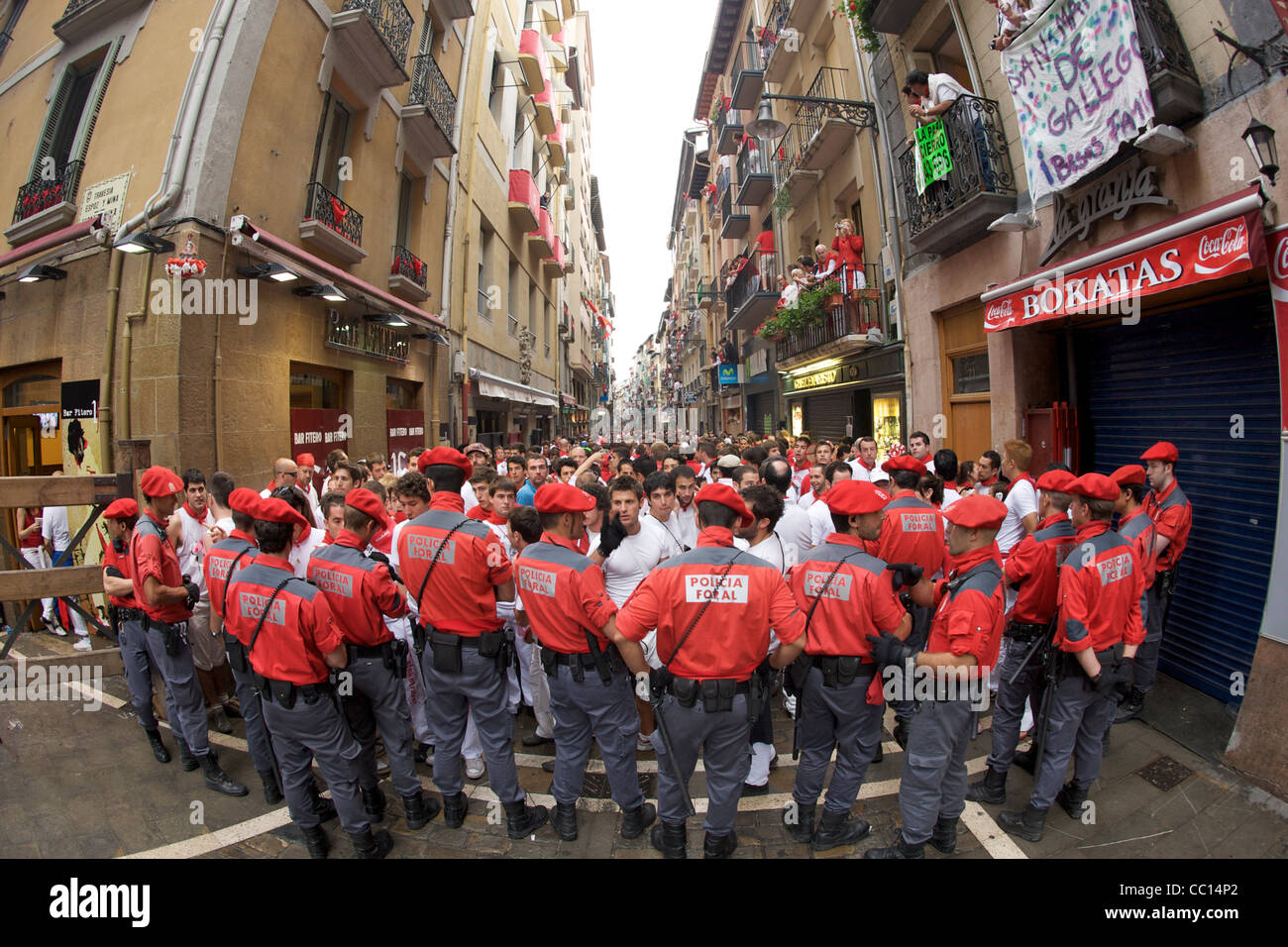 Police holding back runners prior to the morning encierro (bull run) during the festival of San Fermin in Pamplona, Stock Photo